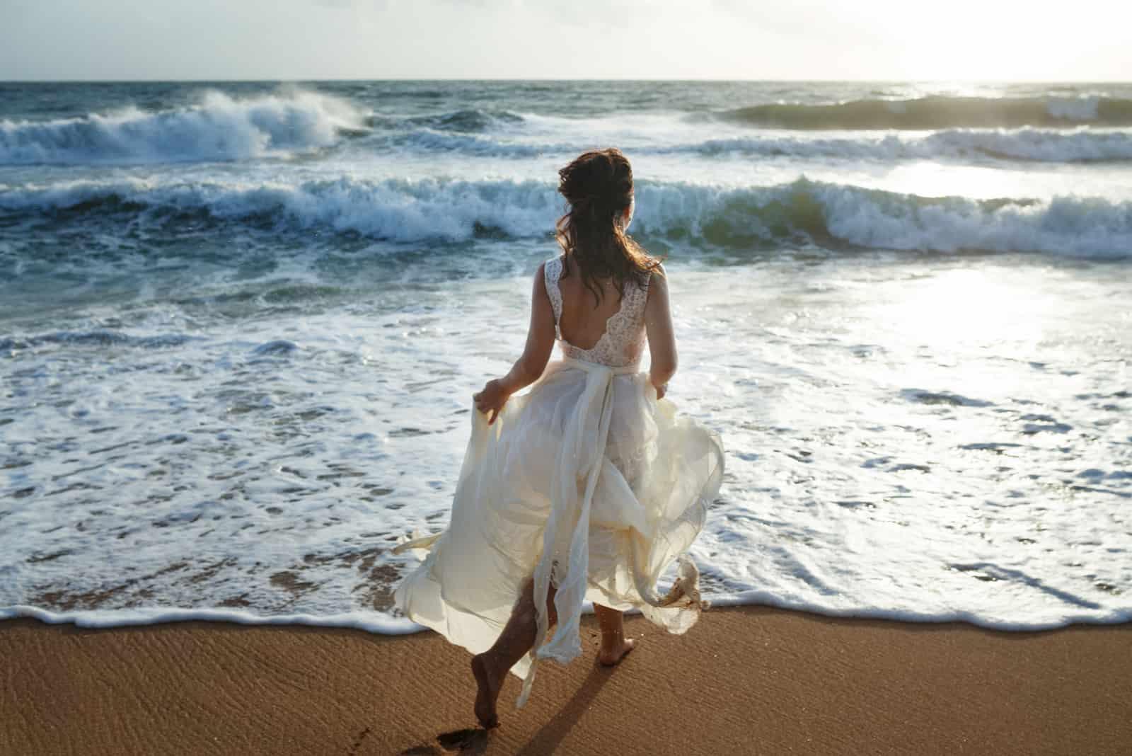 Schöne Braut, die am Strand läuft