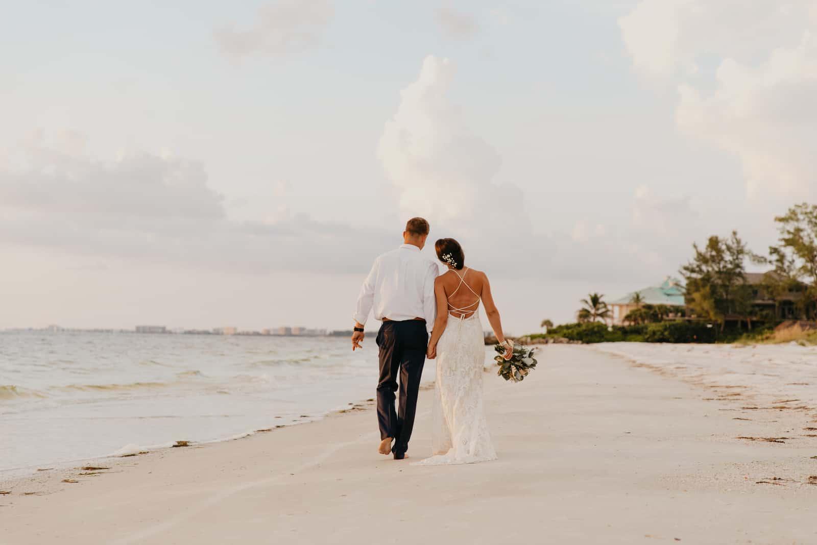 Schöne Braut und Bräutigam spazieren am Strand
