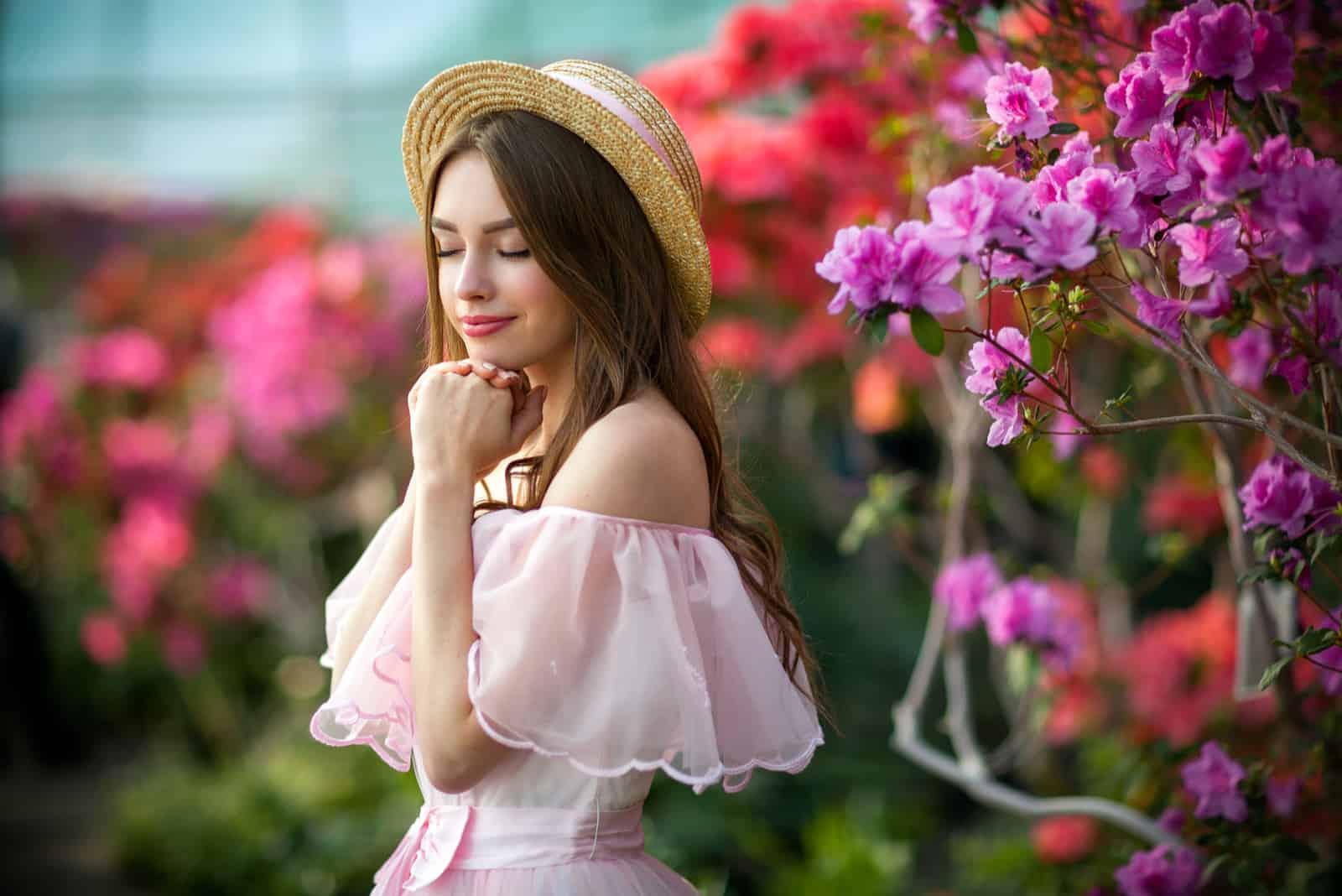 Schönes Mädchen in rosa Vintage-Kleid und Strohhut