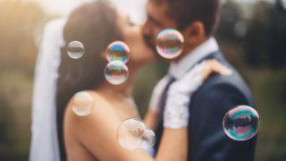 Hochzeitspaar küsst sich mit Blasen herum