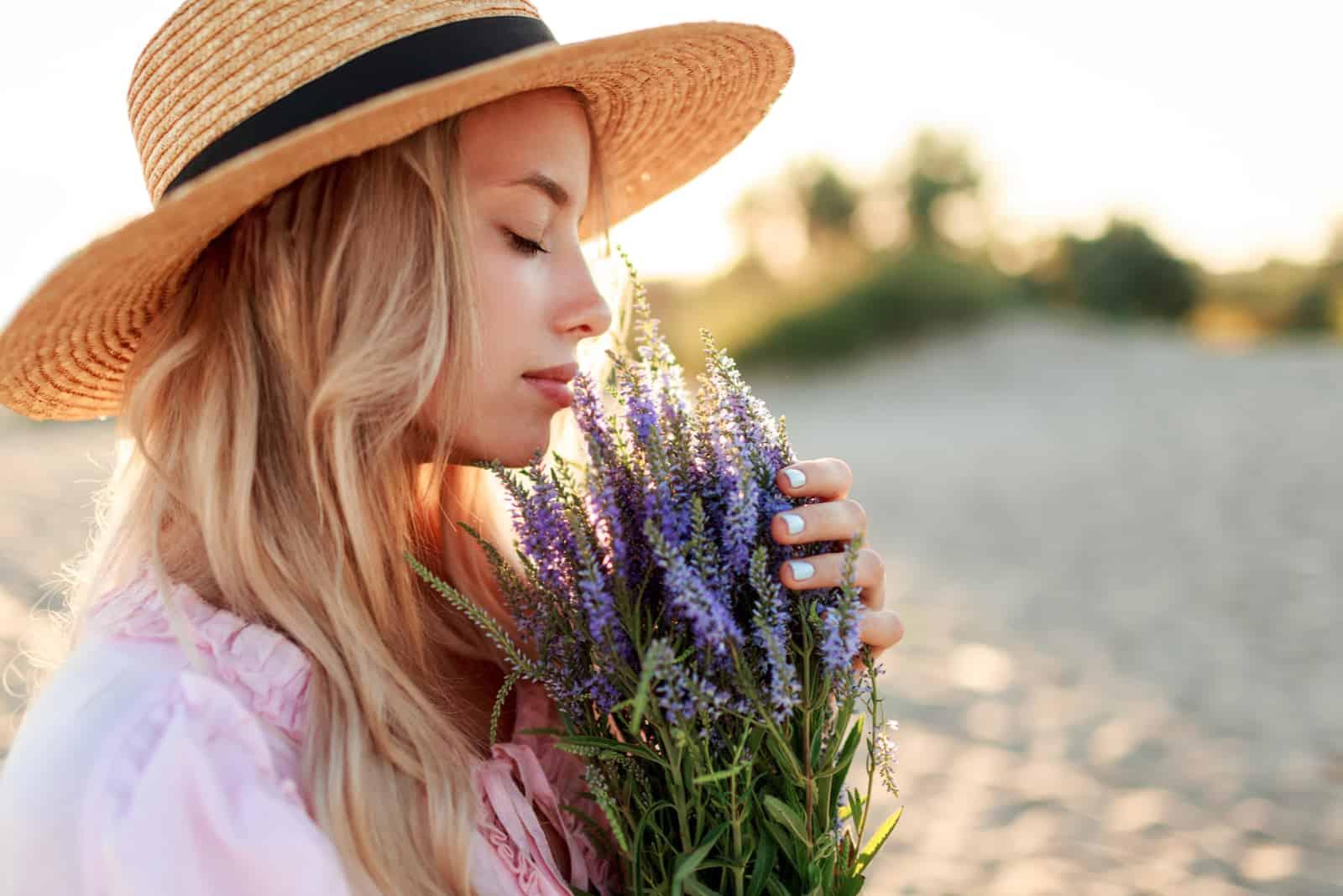 charmantes blondes Mädchen mit Strohhut riecht nach Blumen