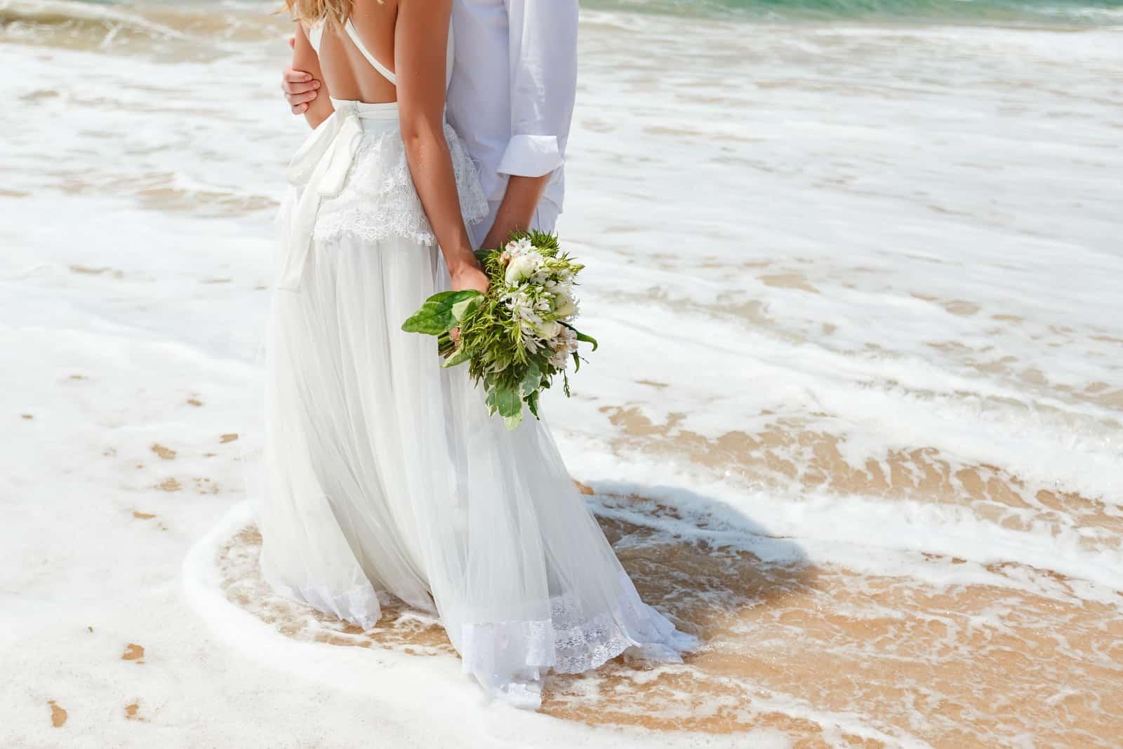 das Brautpaar steht am Strand