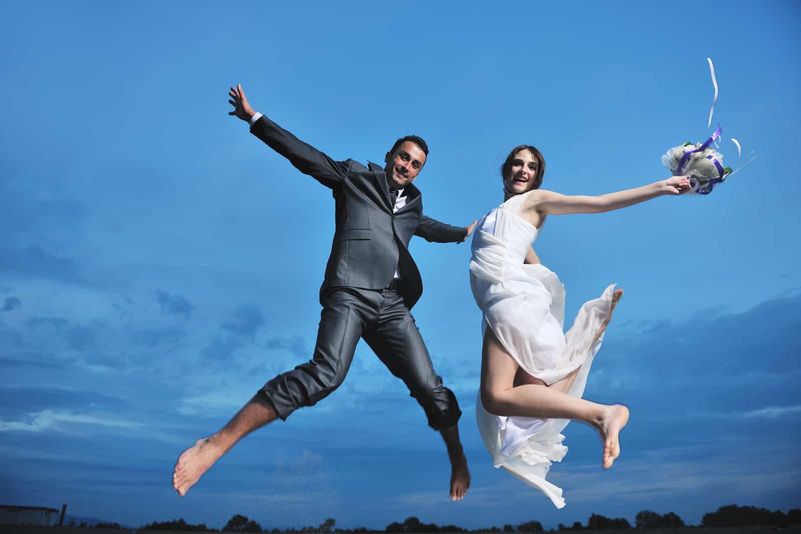 glückliches gerade verheiratetes junges Paar, das feiert
