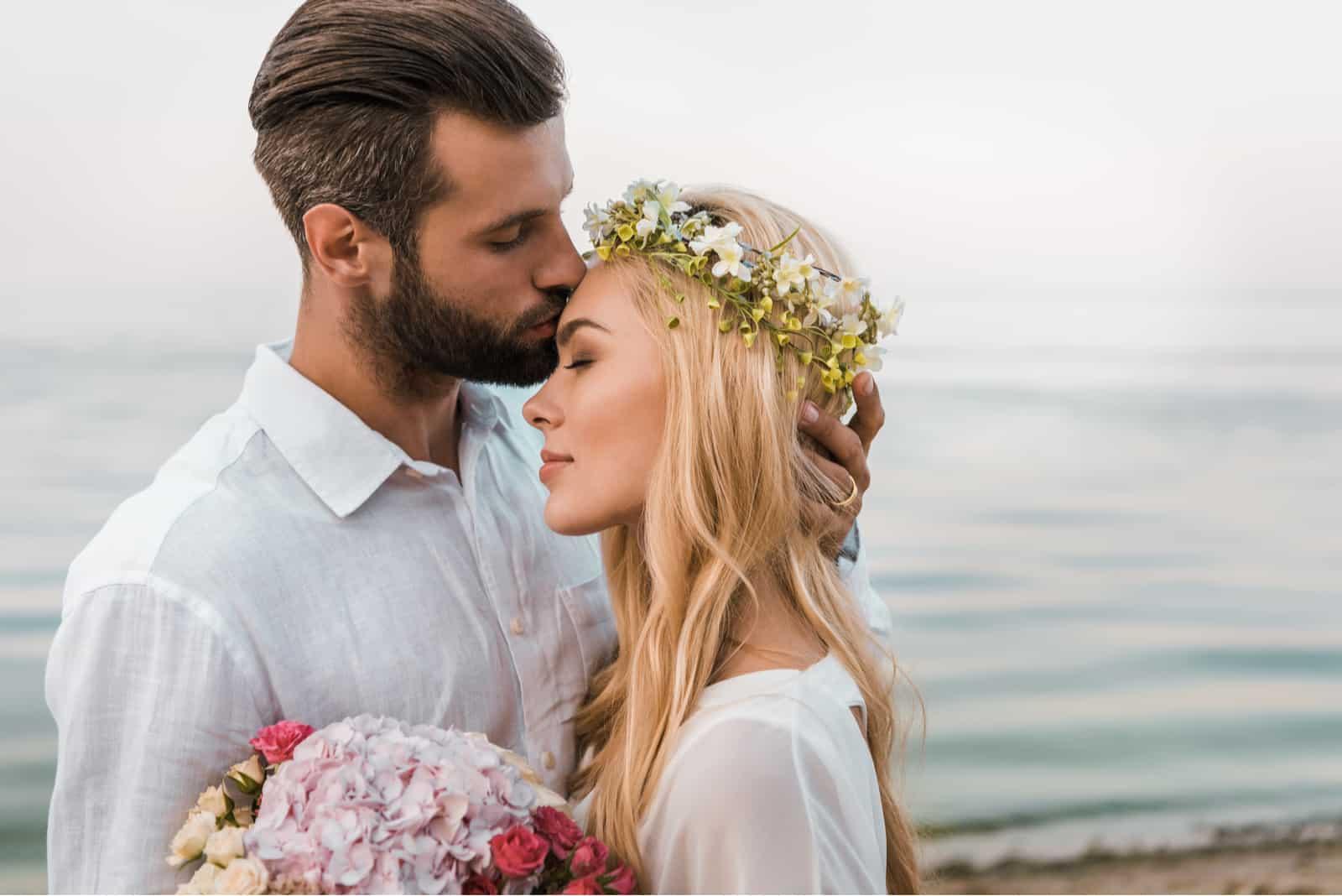 hübscher Bräutigam küsst attraktive Braut in die Stirn am Strand