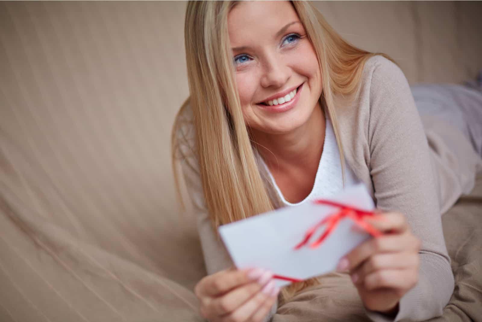 junge lächelnde Frau mit Valentinsbrief