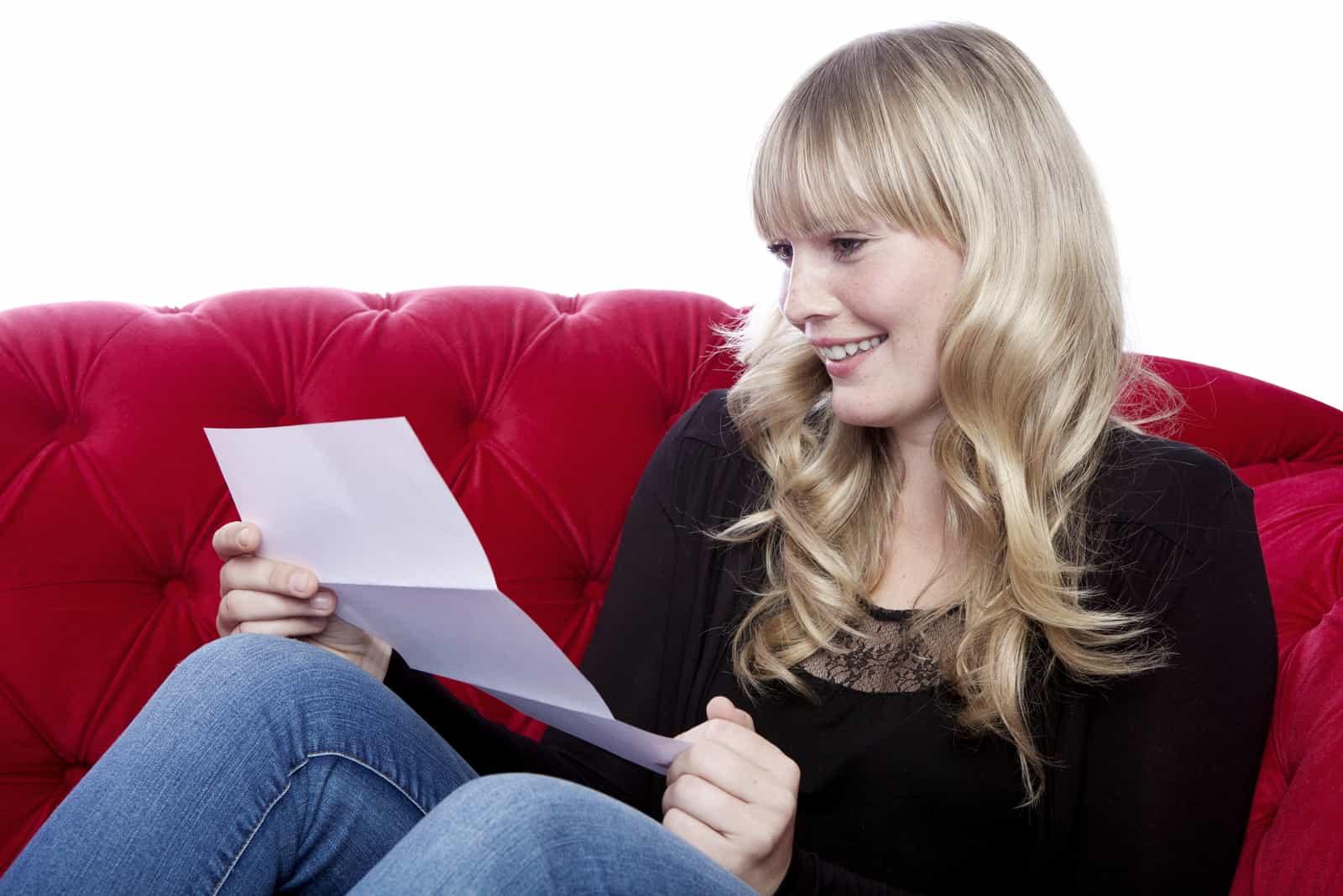 junges blondes Mädchen las auf rotem Sofa einen Brief