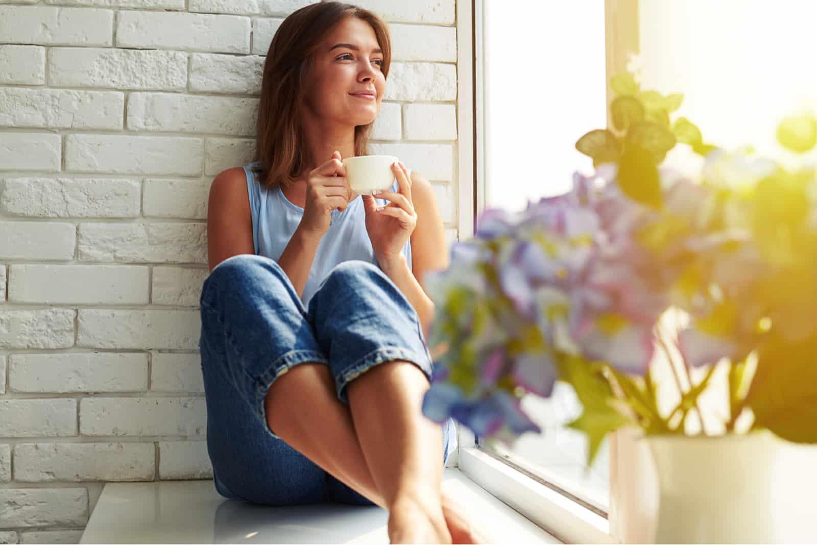 lächelnde Frau sitzt auf der Fensterbank