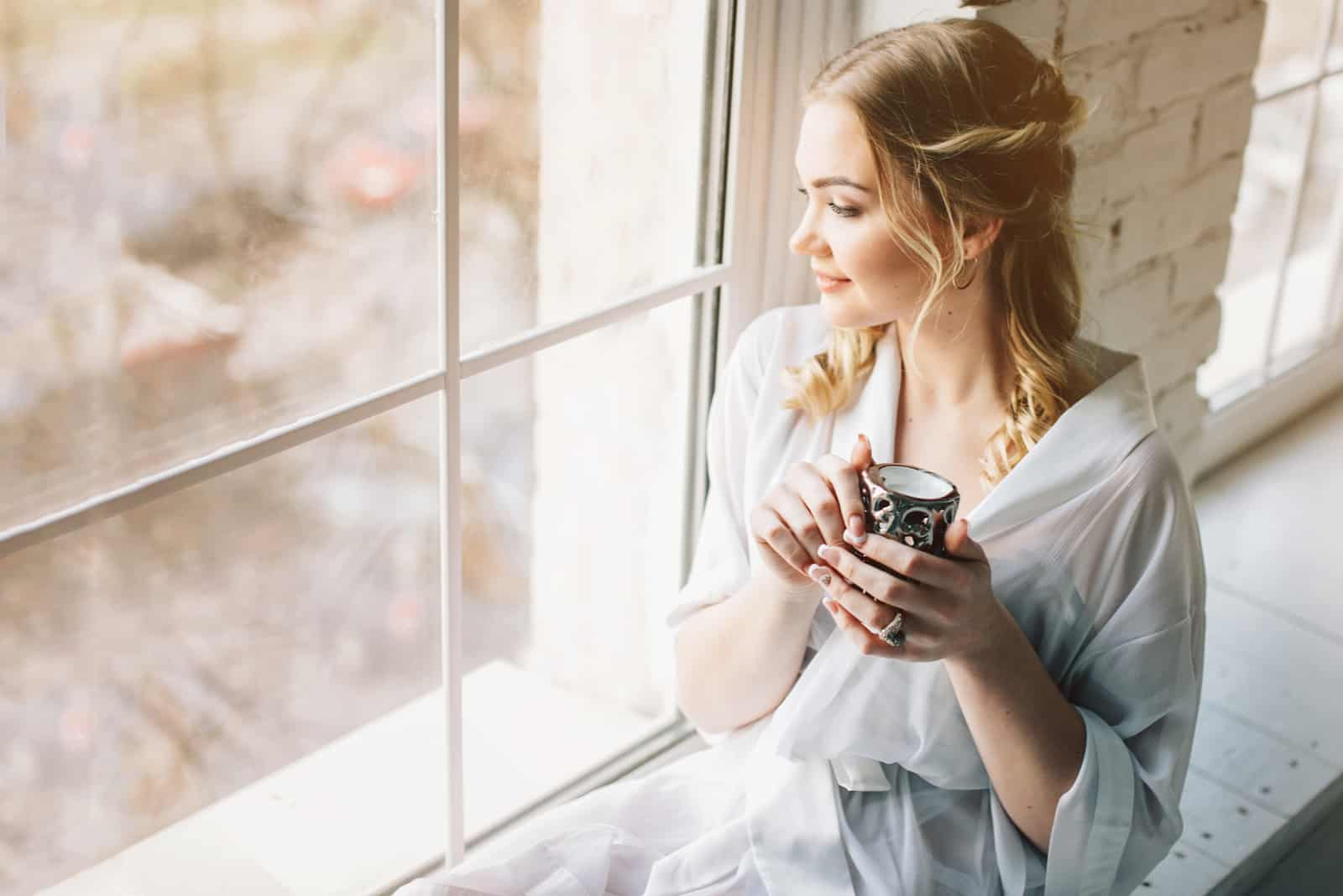 schöne junge Frau am Fenster