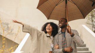 Paar teilt sich einen Regenschirm und genießt den Regen