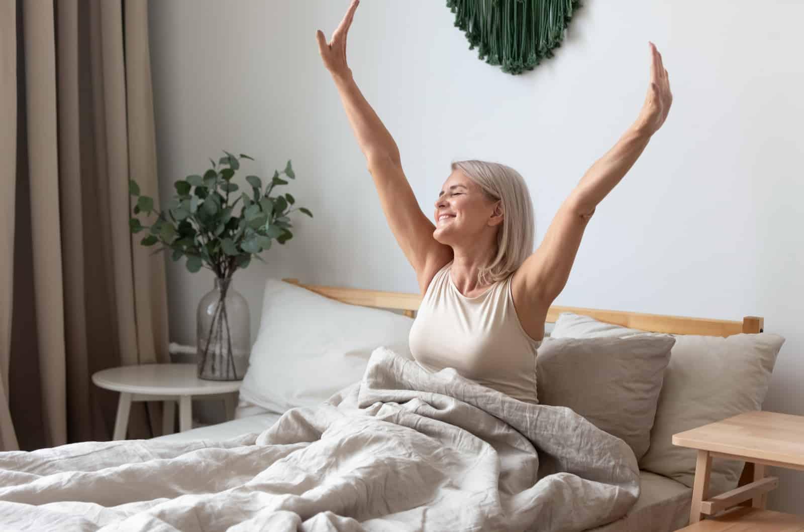 Frau im Bett hebt die Arme in die Luft