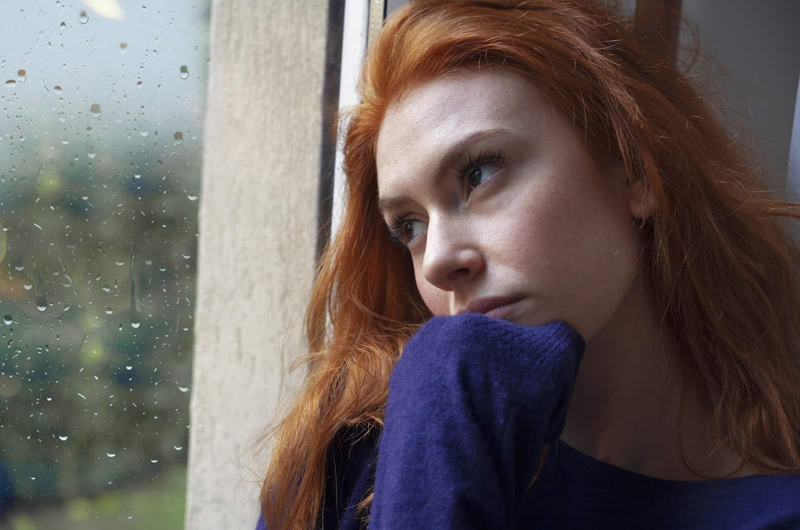Frau traurig, die durch das Fenster schaut