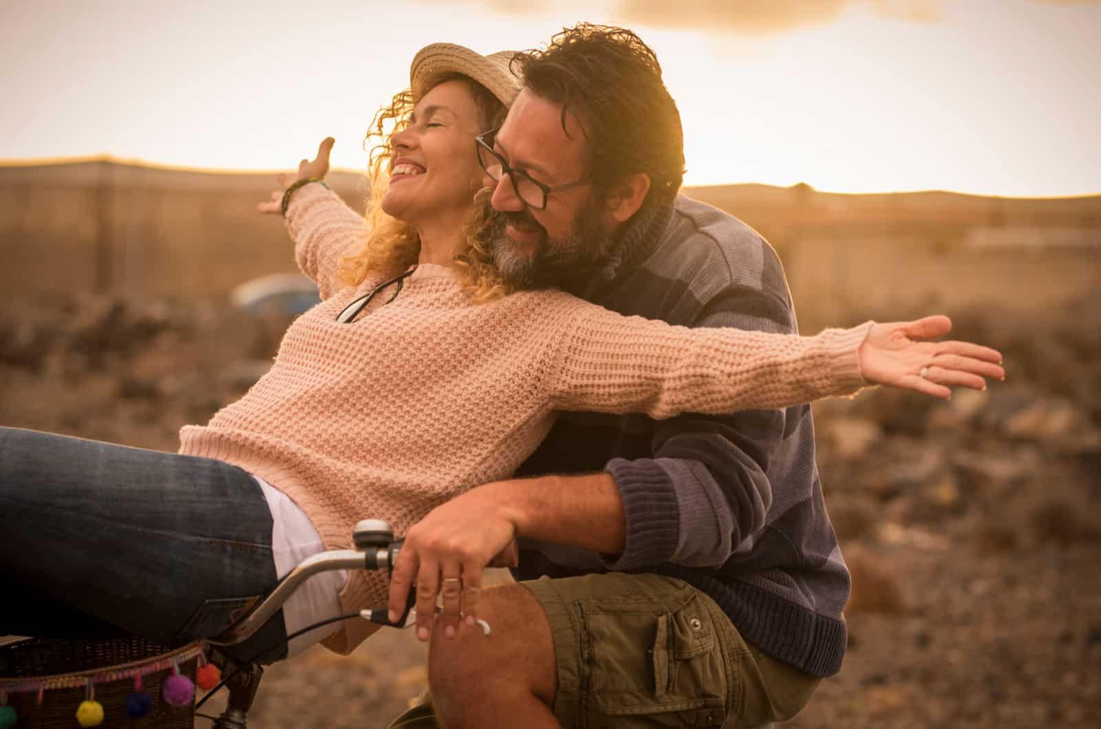 Frau und Mann fahren Fahrrad und lachen