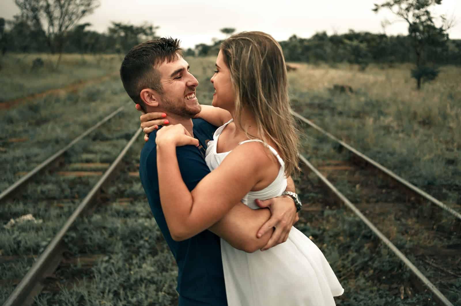 Mann und Frau posieren auf Bahngleisen