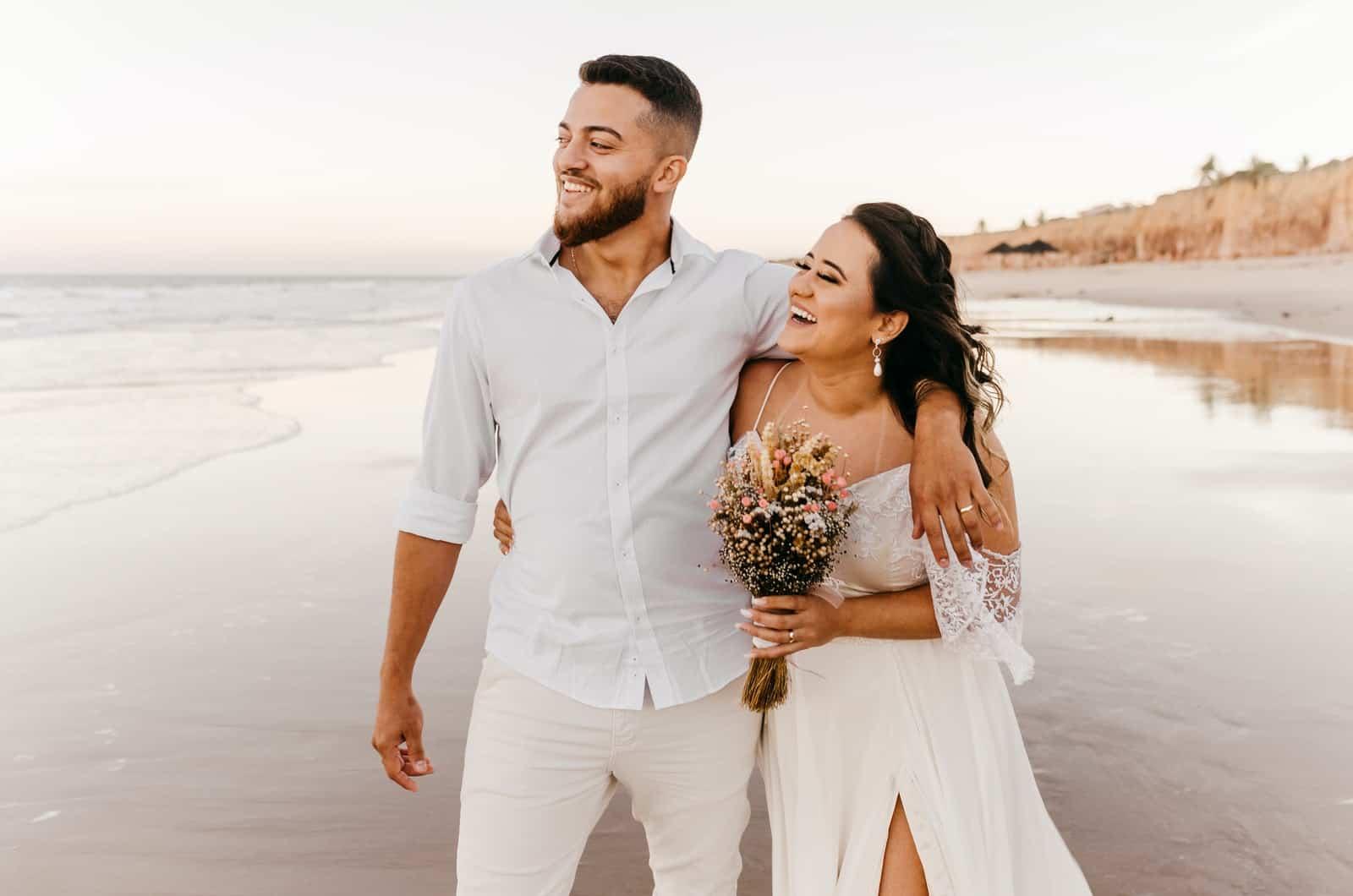 Paar mit Blumenstrauß am Strand spazieren