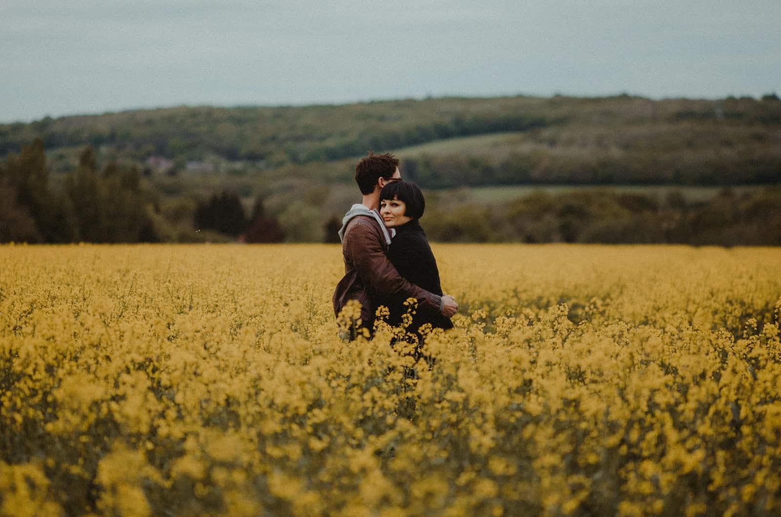 Paar umarmt sich auf einem Feld